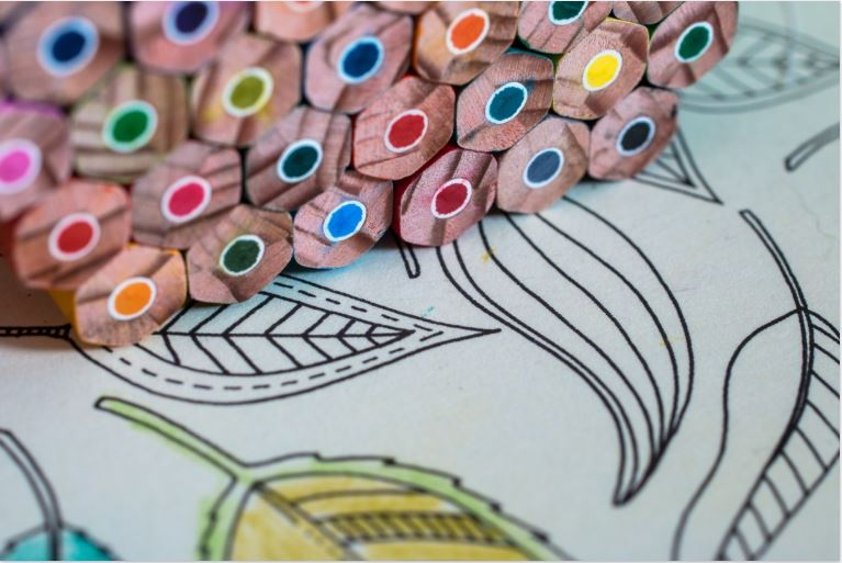 Colored art pencils stacked on some artwork