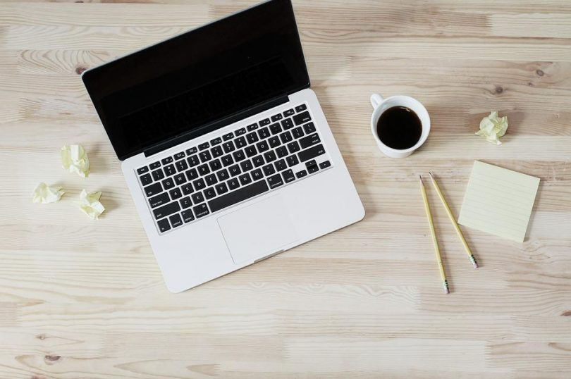 Laptop with coffee cup and pencils next to it