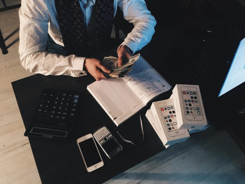 A man sitting at a desk counting money.