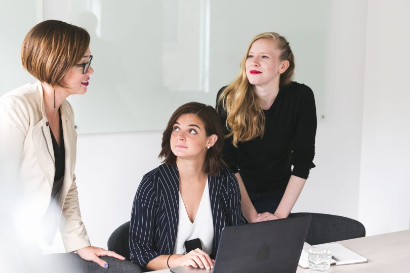 Three business women talking at a desk