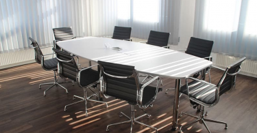 An office board room with eight empty chairs