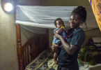 A woman holds a baby as she stands in front of a bed