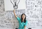 A woman holding up a drawing of a lightbulb indicating she is coming up with ideas.