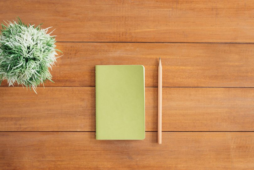 A notepad and pencil on top of a table ready to start planning ideas.