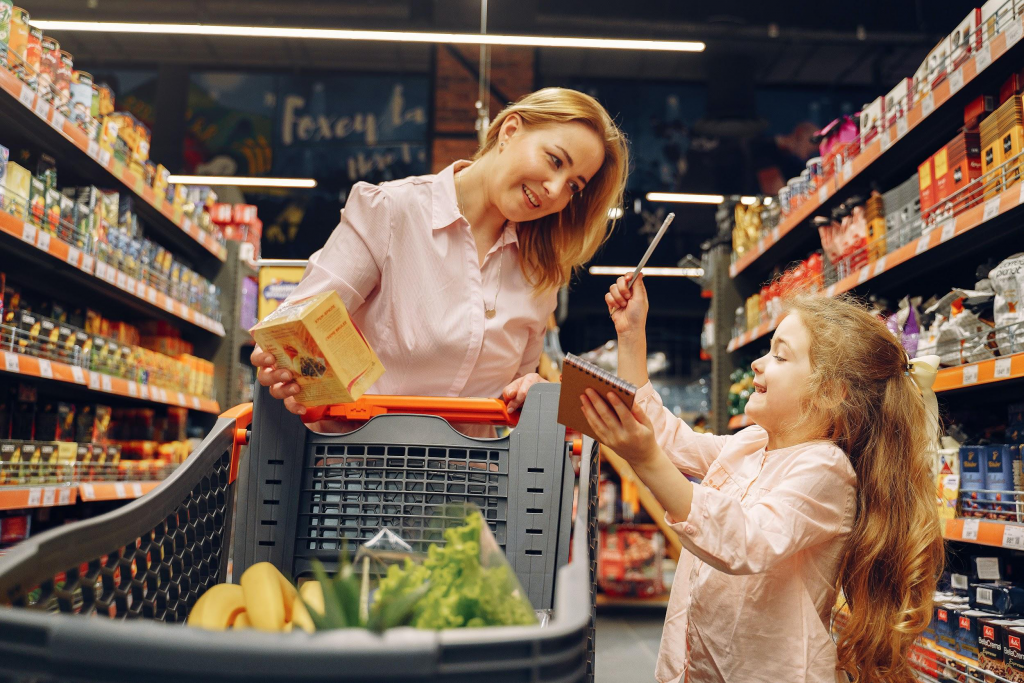 A woman and her young daughter buying groceries from a supermarket