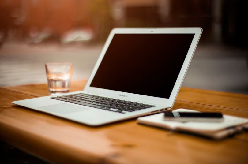 A MacBook Pro resting on a wooden table is used to provide intelligent content management