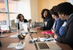 A group of women sat around a desk discussing creating marketing ideas for a new business.
