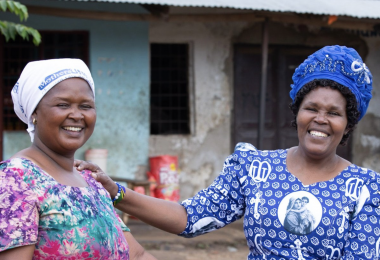 Two women stand in front of a building and smile about the support they've received from Five Talents UK