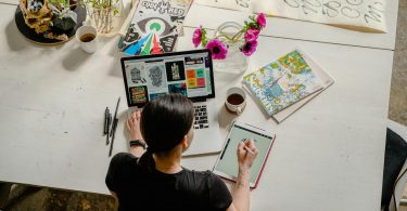 Woman sat at a desk drawing on a tablet to create images for an art business.