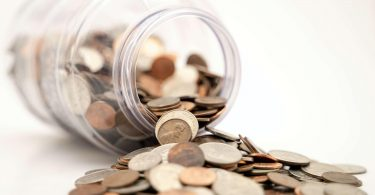 Coins raised from crowdfunding spilling out of a jar