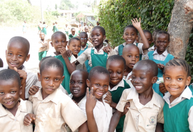 A group of school children stand by a tree and bush as they wait to start their lessons at The Mustard Seed Project school