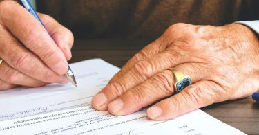 Someone using a pen to sign a will that includes a legacy fundraising donation.