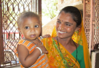 An Indian women holds a baby and smiled because Shanti Life has helped provide them with access to sanitation