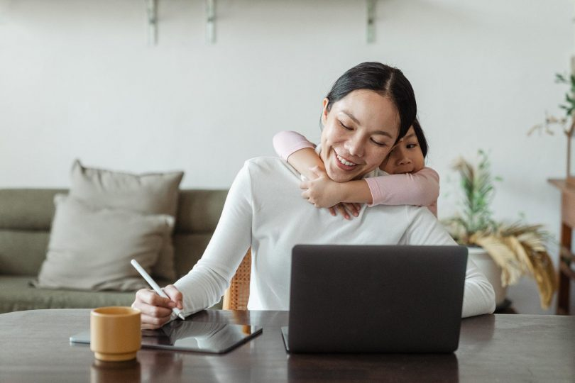 A mum sitting at a table with a laptop planning out a home business idea.