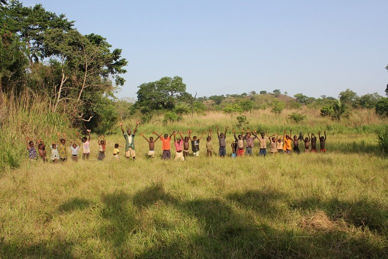 A group of people standing in a field raise their arms to show their gratitude for the support provide to them by LifeLine Network International