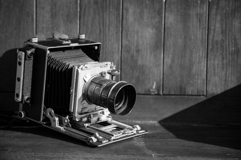 An old black and white camera set on a wooden table isn't enough to start a photography business