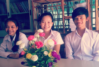 Three Cambodian children site behind a bunch of mult-coloured flowers and smile into the camera because they're received support from Golden Futures