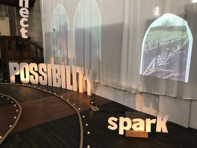 A stage with individual, illuminated signs that say spark and possibility to demonstrate the positive impact Trust Leeds has on people's lives