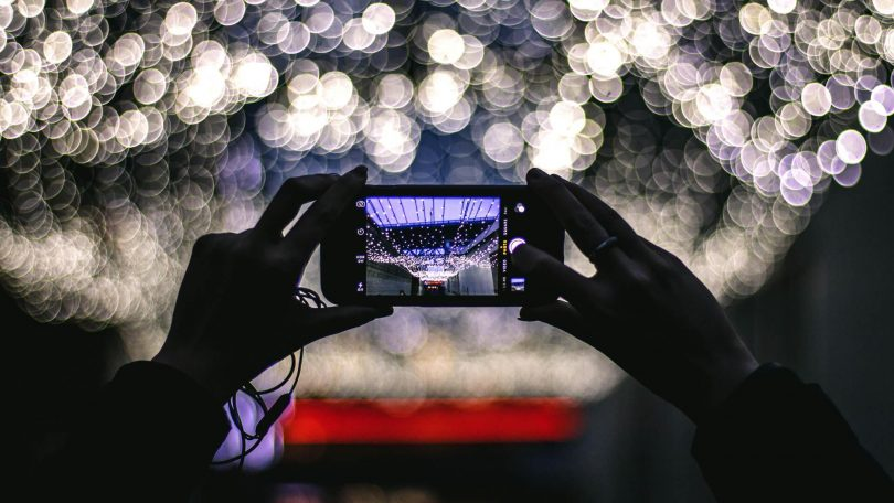 Someone holding up their smartphone to take a photo of some lights.